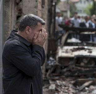 A man reacts next to a burnt out vehicle in Kumanovo, Macedonia
