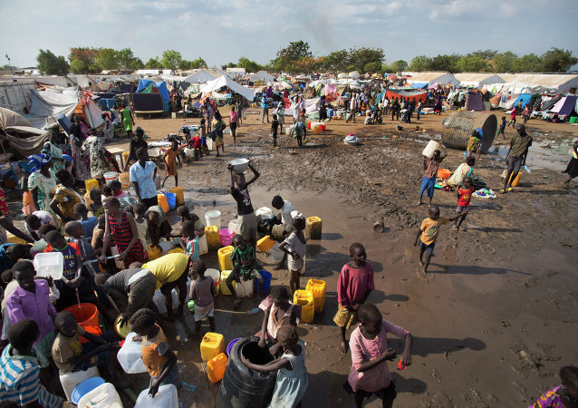In this file photo of Sunday Dec. 29, 2013 file photo, displaced people gather around a water truck to fill containers at a United Nations compound which has become home to thousands of people displaced by the recent fighting, in the capital Juba, South Sudan.