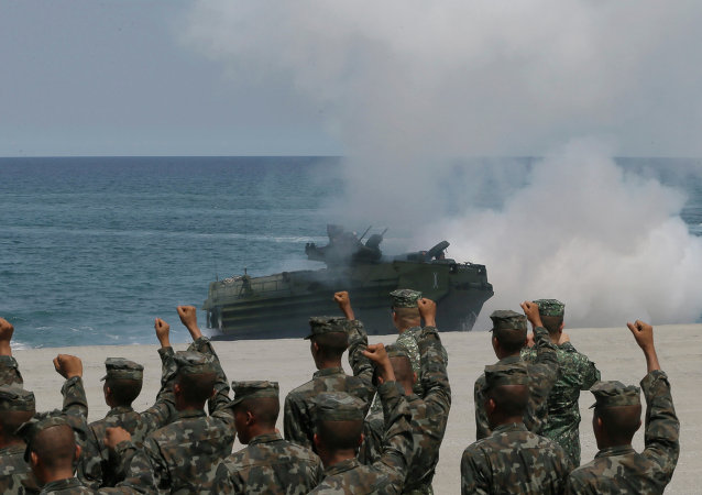 Philippine Marines cheer as a U.S. Navy AAV (Amphibious Assault Vehicle) storms the beach during a combined assault exercise near the contested reef in the South China Sea.