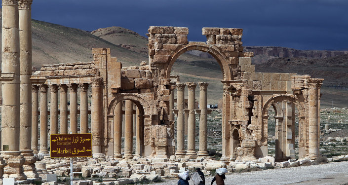 A file picture taken on March 14, 2014 shows Syrian citizens walking in the ancient oasis city of Palmyra, 215 kilometres northeast of Damascus.