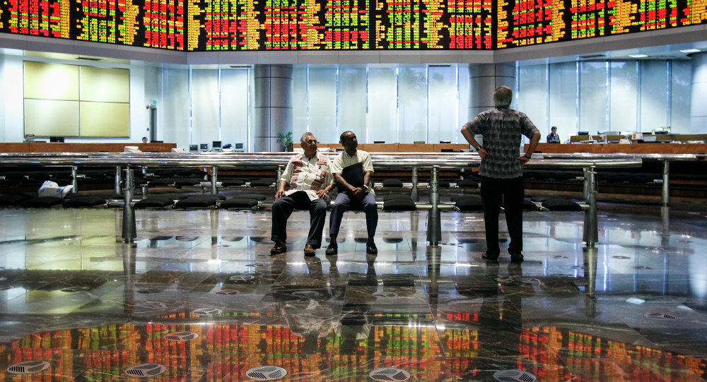 Malaysian men watch the trading board at a private stock market gallery in Kuala Lumpur, Malaysia on Tuesday, May 12, 2015