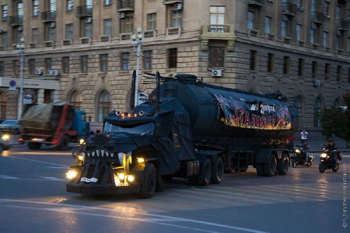 Mad Max driving through the streets of Volgograd, with a banner on its oil tank featuring the city's historic name - Stalingrad.