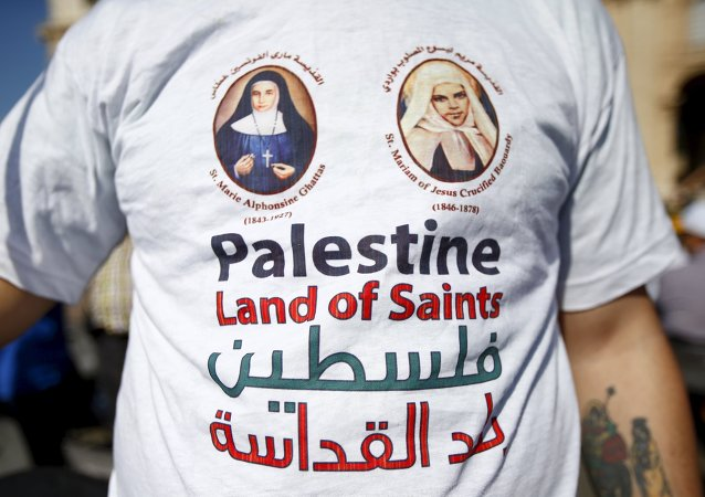 A member of the faithful wears a t-shirt with the pictures of the two Palestinian nuns being canonised before Pope Francis leads a ceremony for the canonisation of four nuns at Saint Peter's square in the Vatican City, May 17, 2015
