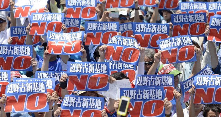 Protesters raise placards during a rally to oppose the transfer of a key U.S. military base within the prefecture, at a baseball stadium in the prefectural capital Naha on Japan's southern island of Okinawa, in this photo taken by Kyodo May 17, 2015