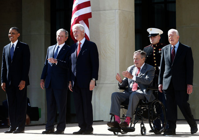 President Barack Obama stands with former presidents George W. Bush, Bill Clinton, George H.W. Bush, and Jimmy Carter.