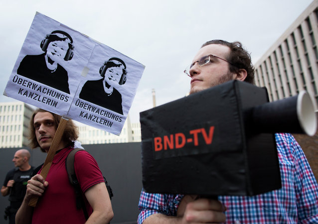 Demonstrators hold a poster showing a portrait of German Chancellor Angela Merkel reading surveillance Chancellor and a fake surveillance camera during a protest against the surveillance by the US National Security Agency, NSA.