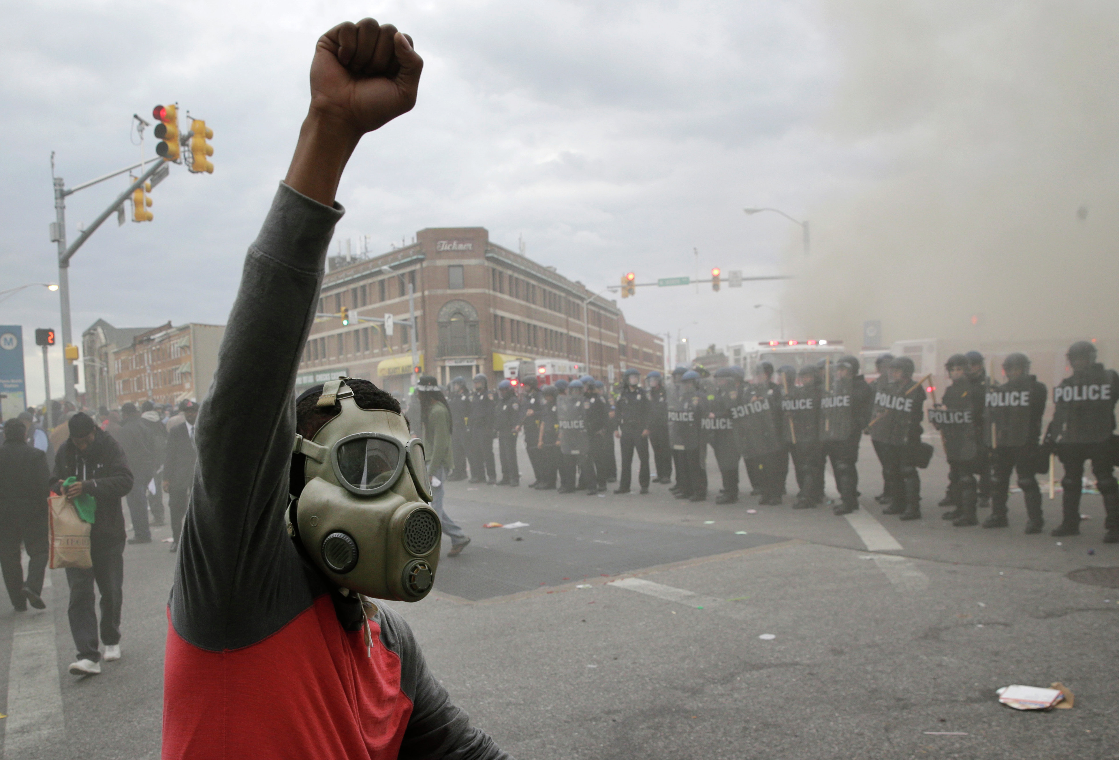 A demonstrator raises his fist as police stand in formation as a store burns, Monday, April 27, 2015, during unrest following the funeral of Freddie Gray in Baltimore