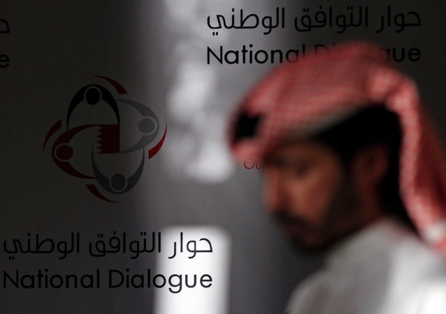 A Bahraini man walks past a display that reads, national dialogue in Arabic and English.