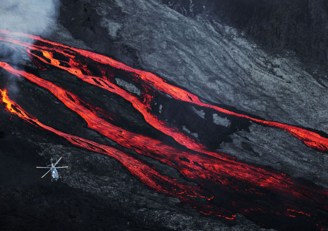 A helicopter flies overhead as lava flows out of the Piton de la Fournaise volcano
