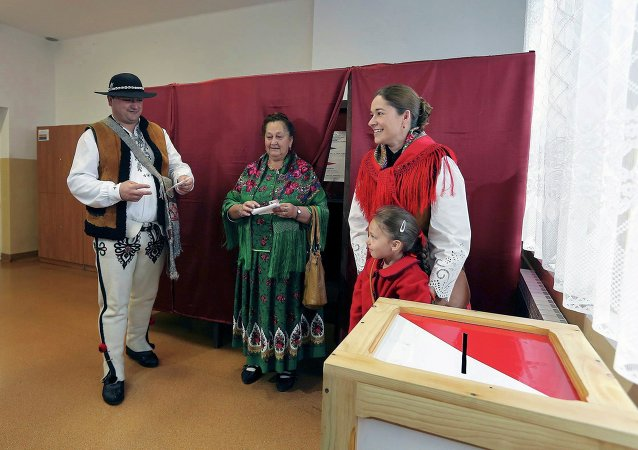 People wearing traditional outfits prepare to cast their ballots during the second round of presidential elections at a polling station in Zakopane, Poland May 24, 2015