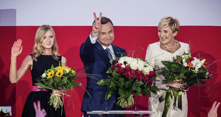 Andrzej Duda (C), presidential candidate of Law and Justice (PiS) right wing opposition party celebrates with his wife Agata (R) and daughter Kinga (L) after the announcement of the exit poll results of the second round of the presidential election in Warsaw, on May 24, 2015