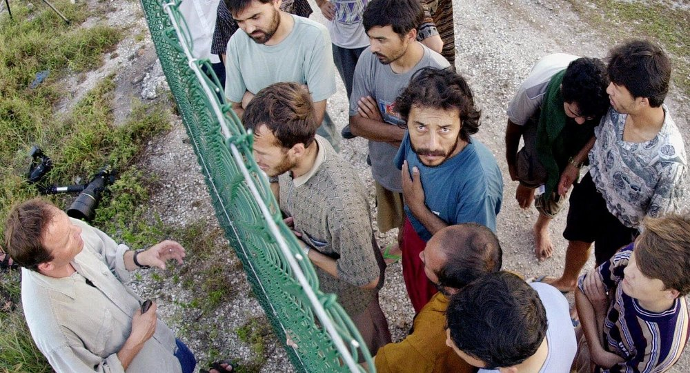 Asylum seekers at Australia's detention center on the island of Nauru gather on one side of a fence to talk with international journalists about their journey that brought them there.