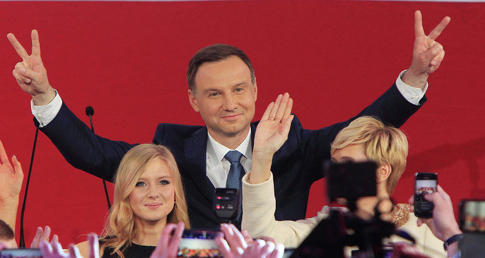 Opposition candidate Andrzej Duda, with daughter Kinga greet supporters as first exit polls in the presidential runoff voting are announced, in Warsaw, Poland, Sunday, May 24, 2015
