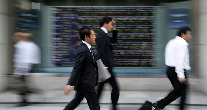 People walk past an electronic stock board of a securities firm in Tokyo.