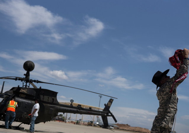 A soldier secures the rotor blades of his Bell OH-58 Kiowa helicopter while dropping it off to be stored at the boneyard at the Aerospace Maintenance and Regeneration Group on Davis-Monthan Air Force Base in Tucson, Arizona