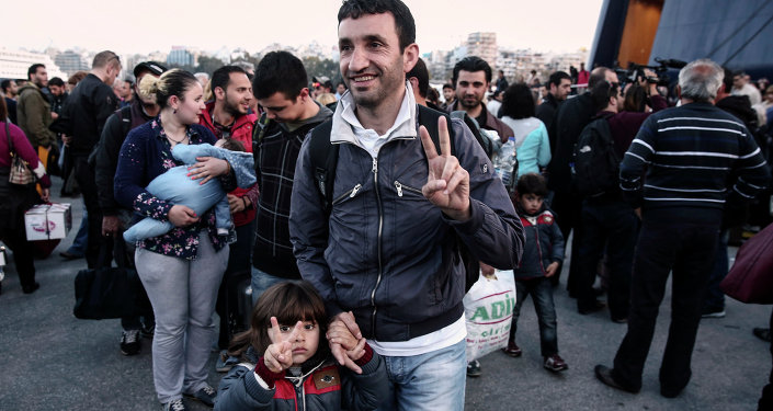 A migrant from Syria and his child flash a victory sign as they arrive from the eastern Aegean island of Lesvos at the port of Piraeus, near Athens