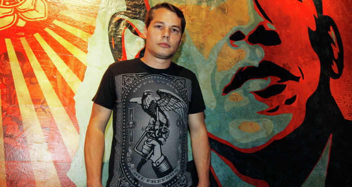 Artist Shepard Fairey poses for a portrait in front of a mural he created that was inspired by Barack Obama.