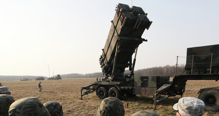 Polish and US soldiers look at a missile defense battery during joint exercises.
