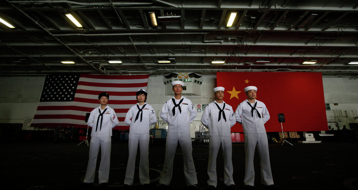 Chinese-American Navy sailors stand in front of the China's and American national flags on the aircraft carrier USS George Washington in Hong Kong Wednesday Nov. 9, 2011.