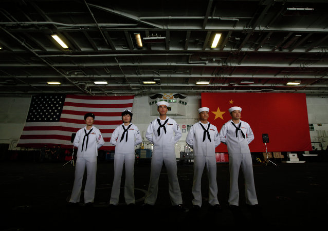 Chinese-American Navy sailors stand in front of the China's and American national flags on the aircraft carrier USS George Washington.