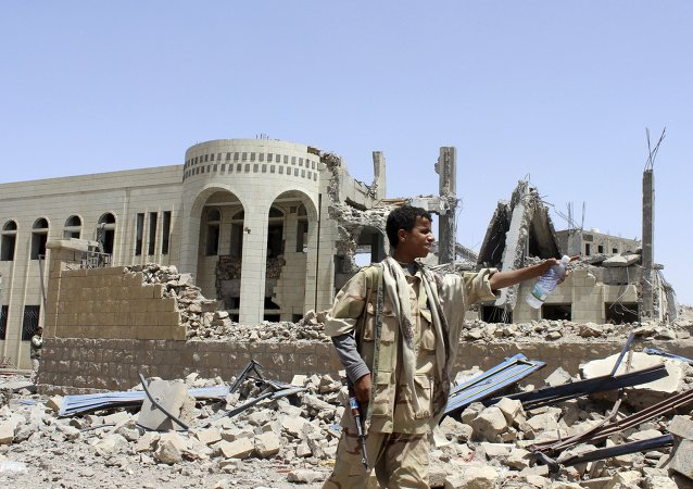Houthi militant stands in front of a court building, which was damaged in a Saudi-led air strike in Saada May 31, 2015