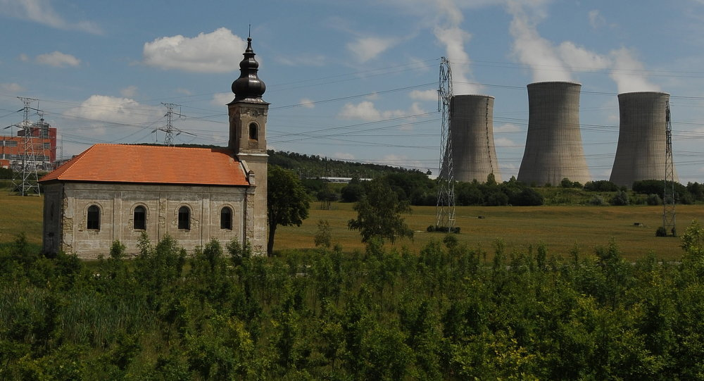 Steam cooling towers of the Mochovce nuclear power plant release steam behind a small church