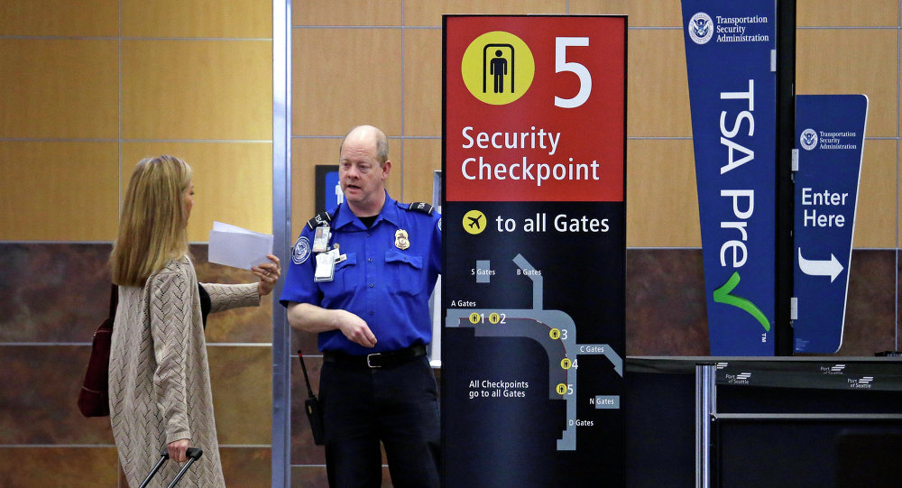 Passenger shows a boarding pass to a TSA agent at a security check-point at Seattle-Tacoma International Airport in SeaTac, Wash