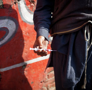 A drug addict holds a needle and syringe.