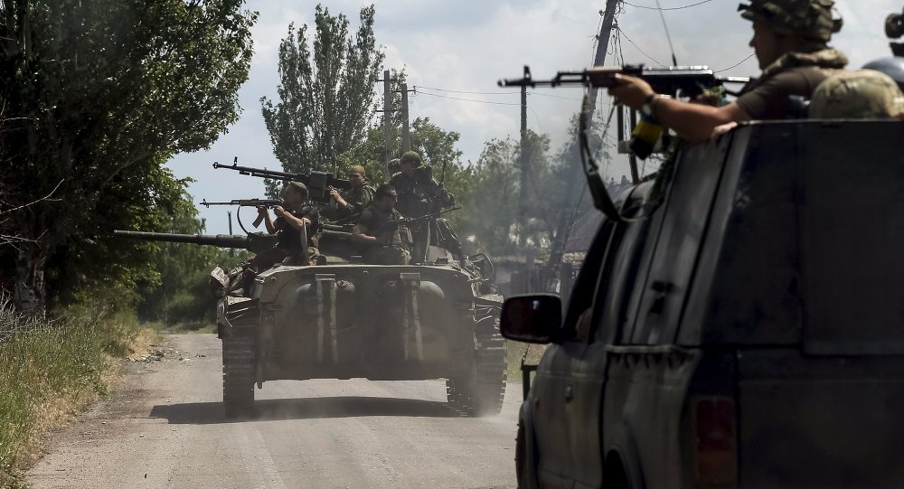 Members of the Ukrainian armed forces ride on an armoured personnel carrier as they patrol the area in the town of Maryinka, eastern Ukraine, June 5, 2015