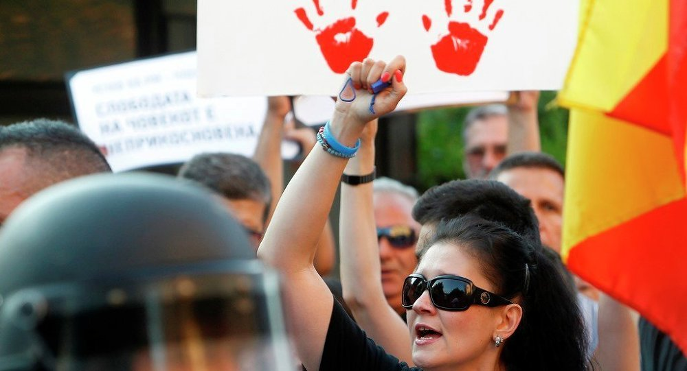 People protest in front of a police cordon set at the approach of the Interior Ministry in Skopje, Macedonia.