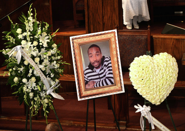 (FILES) In this August 30, 2014 file photo, a photo of Ezell Ford is seen at his funeral service at the First AME Church in Los Angeles