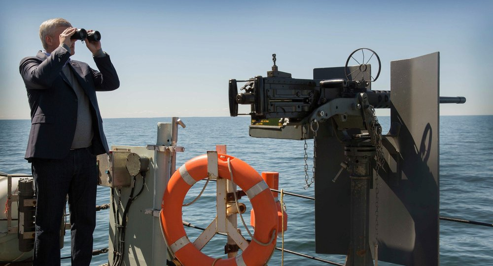 Canada's Prime Minister Stephen Harper views Russian naval vessels while on board the Canadian frigate HMCS Fredericton in the Baltic Sea, June 10, 2015