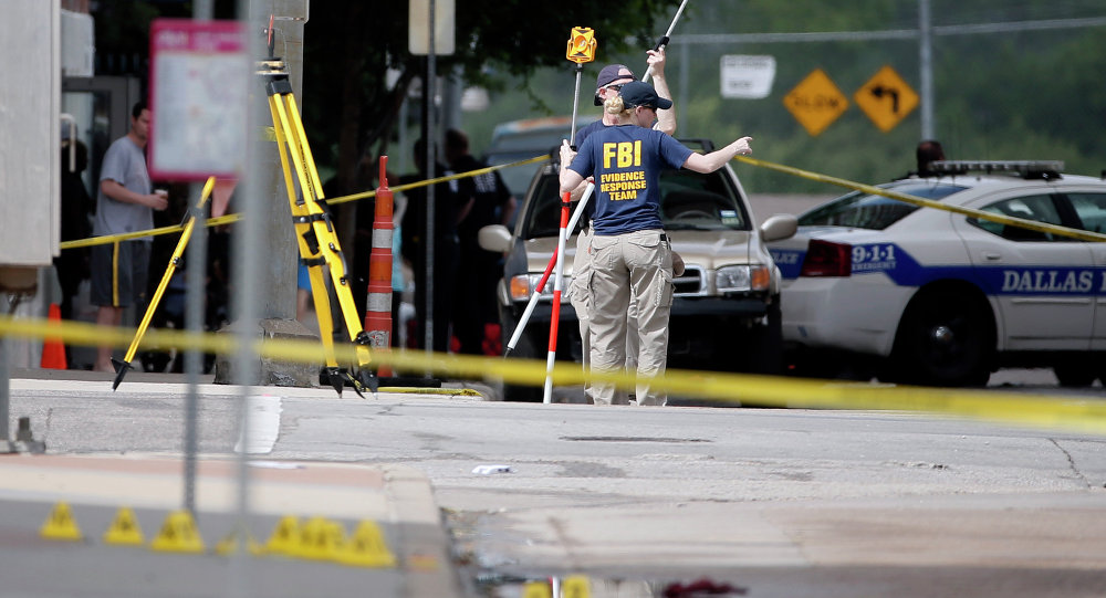 Members of the FBI evidence response team investigate an intersection in front of Dallas police headquarters Saturday June 13, 2015, in Dallas