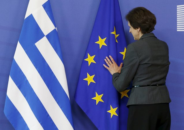 A worker adjusts flags ahead of the meeting between Greek Prime Minister Alexis Tsipras and European Commission President Jean-Claude Juncker at the EU Commission headquarters in Brussels, Belgium, June 3, 2015
