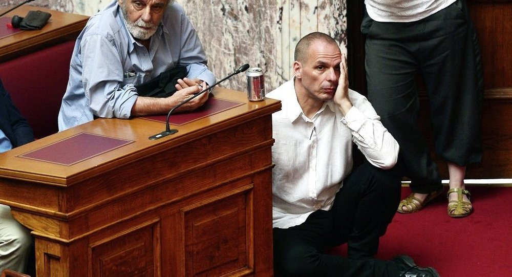 Greek Finance Minister Yianis Varoufakis (L) listens to Prime Minister addressing his MP's and ministers at the Greek Parliament in Athens on June 16, 2015.