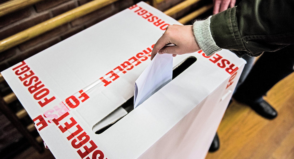 A voter casts a ballot in the voting box wrapped by tapes bearing letters that read: Sealed at a primary school in Copenhagen, Denmark, Thursday morning June 18, 2015