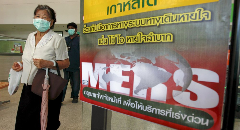 A woman wearing a mask walks past an information banner on Middle East Respiratory Syndrome (MERS) at the entrance of Bamrasnaradura Infectious Diseases Institute at a hospital in Nonthaburi province, on the outskirts of Bangkok, Thailand, June 19, 2015