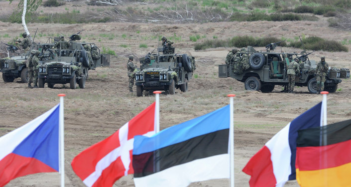Flags wave in front of soldiers who take positions with their army vehicles during the NATO Noble Jump exercise on a training range near Swietoszow Zagan, Poland. file photo