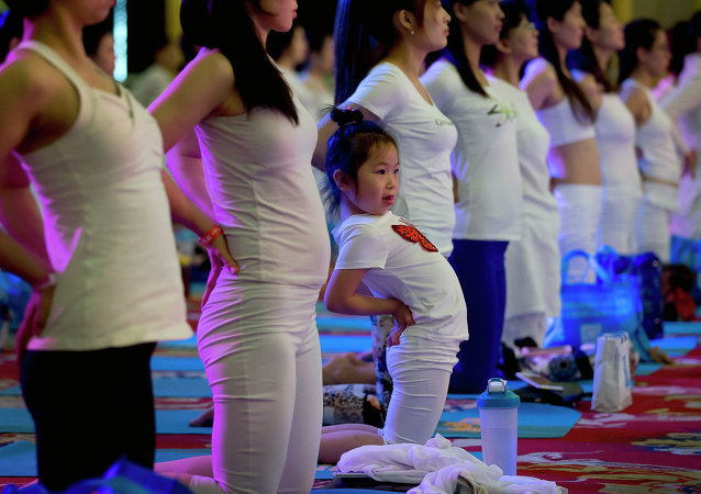 A child performs yoga at a hotel banquet hall to mark the International Yoga Day, in Changping District, on the outskirts of Beijing, China, Sunday, June 21, 2015