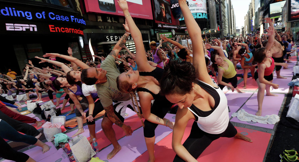 Thousands of New Yorkers are marking the first day of summer by practicing yoga in Times Square