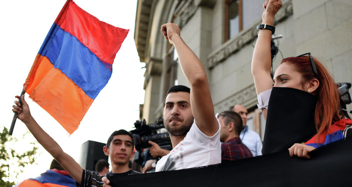 A demonstrator waves an Armenian flag as others raise their fists during a protest against the increase of electricity prices outside the Armenian National Academic Theatre of Opera and Ballet in Yerevan, the capital of Armenia, on June 19, 2015