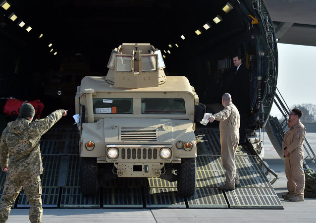 Ukrainian and US servicemen unload armoured cars from a plane at Kiev airport on March 25, 2015