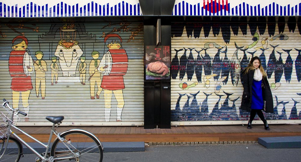 A woman stands in front of a closed shop in the outer part of the Tsukiji fish market, the Jogai Shijo, in Tokyo