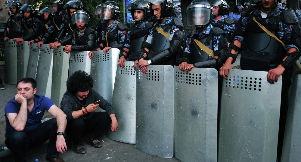 Demonstrators sit on a street in front of a line of riot police during a protest against an increase of electricity prices in the Armenian capital Yerevan on June 24, 2015