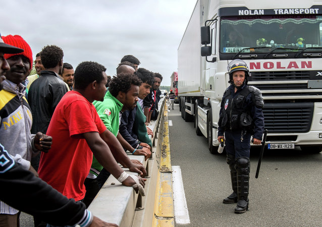 A French riot police officer (CRS) stands holdings his baton as illegal migrants wait to hide in lorries heading for England, in the French northern harbour of Calais, on June 17, 2015