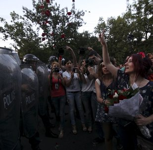 A protester throws rose petals in front of a line of riot police during a rally against a recent decision to raise public electricity prices in Yerevan, Armenia, June 23, 2015