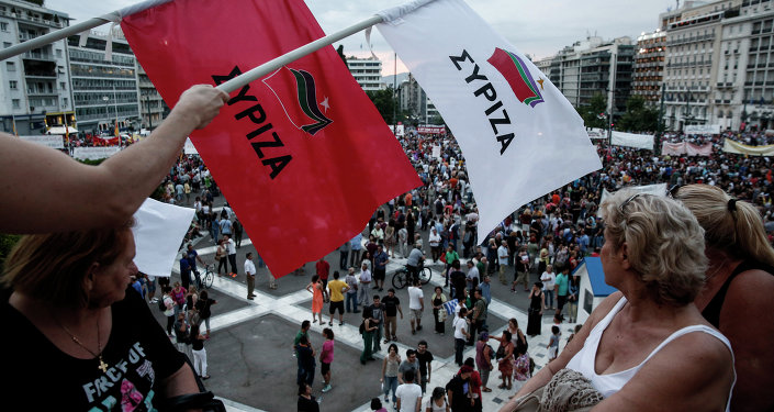 Anti-austerity protesters wave flags of the ruling Syriza party during a rally outside the parliament in Athens, Greece, on Sunday, June 21, 2015