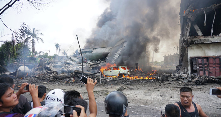 People look at a military plan crash in Medan
