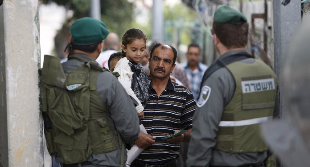 A Palestinian man carrying his daughter shows his identity card to Israeli border policemen at an Israeli checkpoint in the West bank city of Bethlehem June 26, 2015