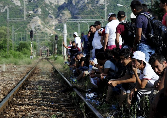 Migrants wait beside railway tracks for trains at Demir Kapia train station in Macedonia, near the border with Greece